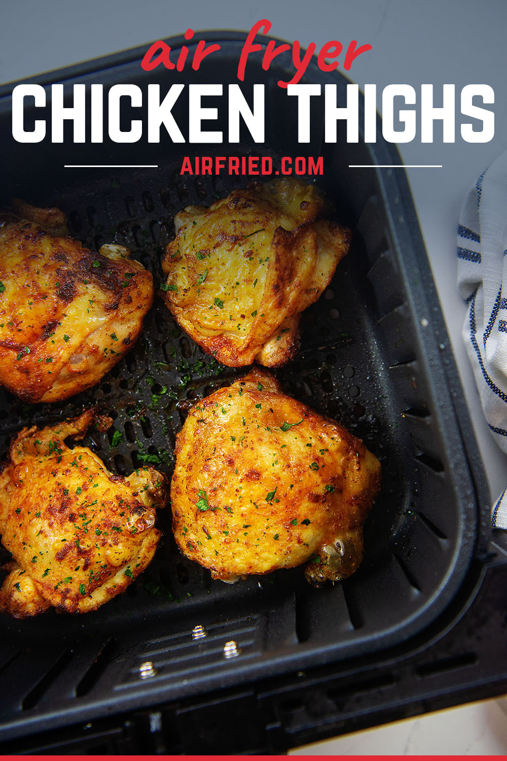 Overhead view of four chicken thighs in an air fryer.