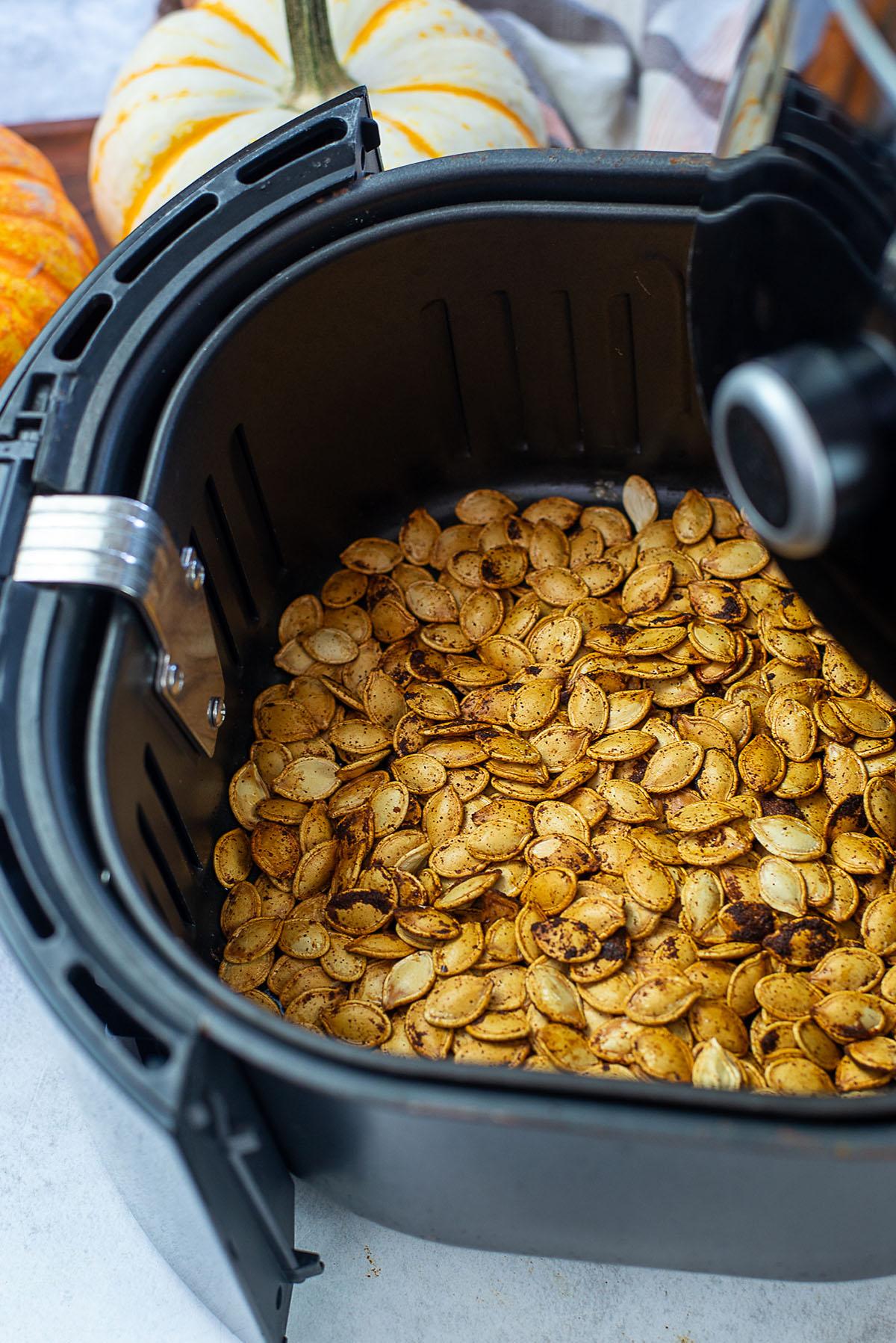 Cooked pumpkin seeds in an air fryer basket