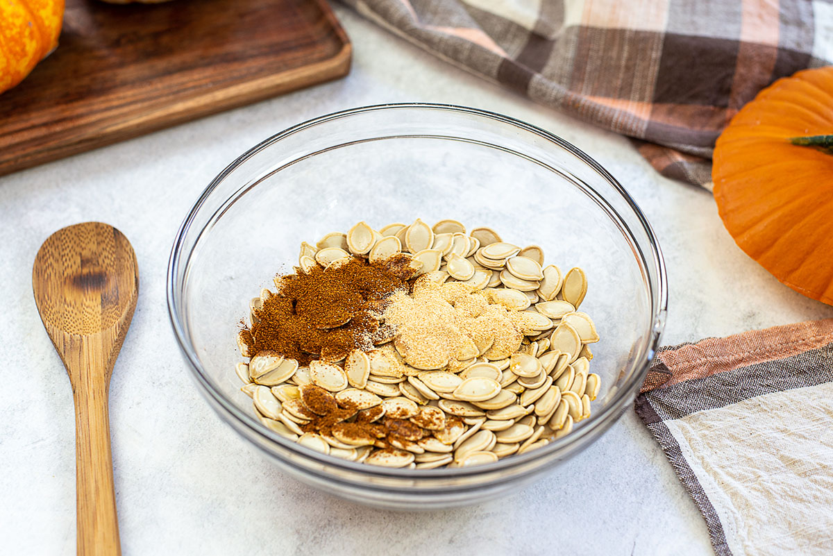 Pumpkin seeds and seasoning in a clear glass bowl.