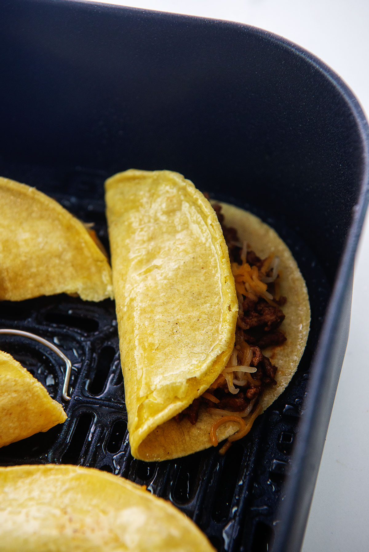 A fried taco in an an air fryer basket