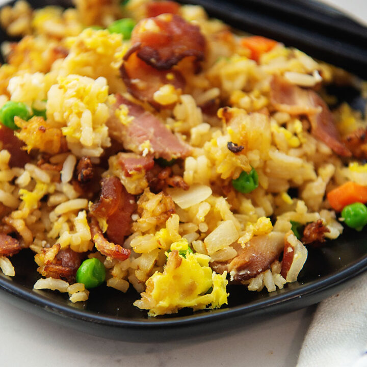 Small black plate with fried rice and chop sticks on it.