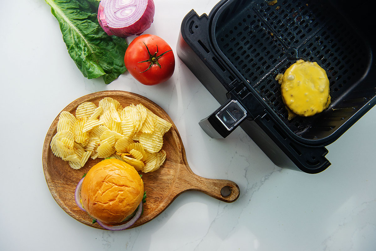 Overhead view of cheeseburger and chips on a wooden plate.
