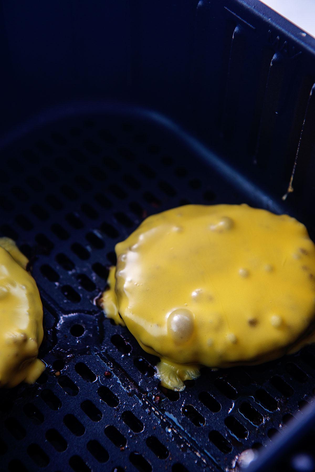 Two cheeseburgers in an air fryer basket.