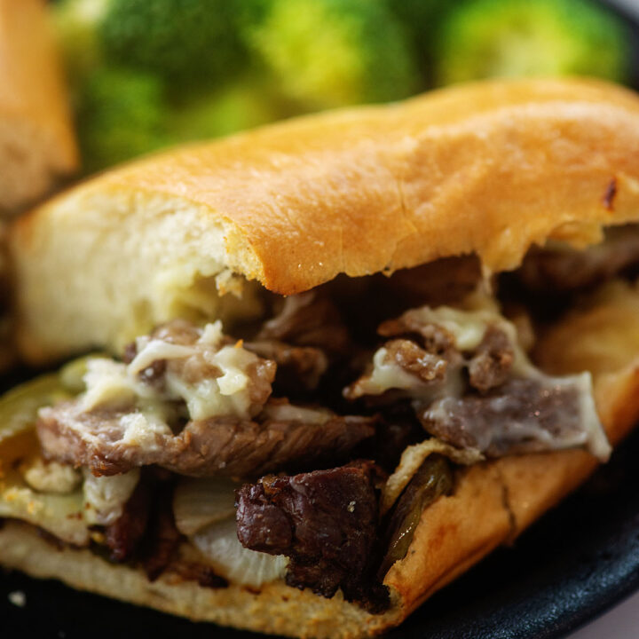 Philly steak sandwich with melted cheese on a black plate.
