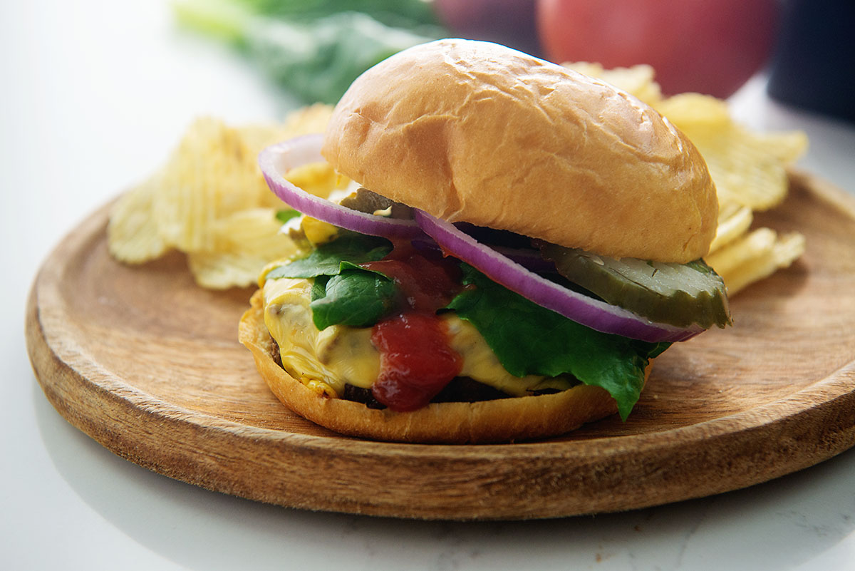 Cheeseburger with onion, pickle, and lettuce