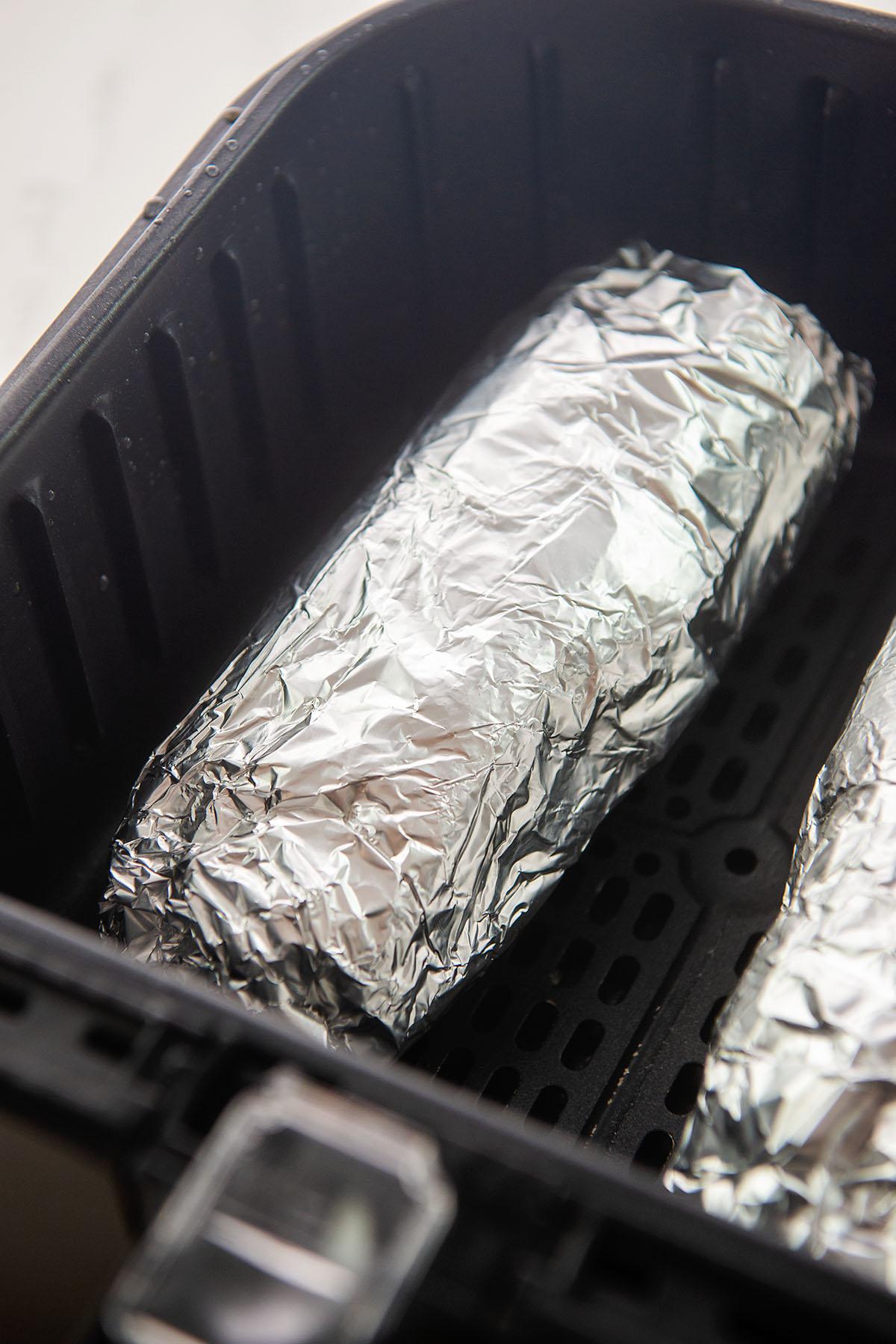 Sandwich wrapped in foil in an air fryer basket.